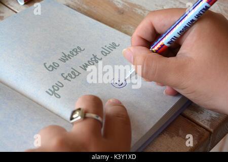 Dessin femme un smiley dans un journal ouvert à une page avec le mantra Rendez-vous où vous vous sentez le plus en vie