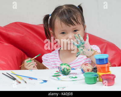 Petite fille la peinture avec le pinceau et les peintures colorées de ce concept de développement des enfants Banque D'Images