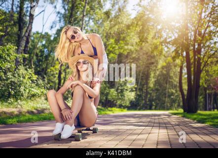 Une photo de belle femme assise sur la planche à roulettes et qui est poussé par son ami. Banque D'Images