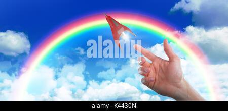 Main de l'homme semblant de toucher un écran invisible contre vue idyllique de cloudscape against sky Banque D'Images