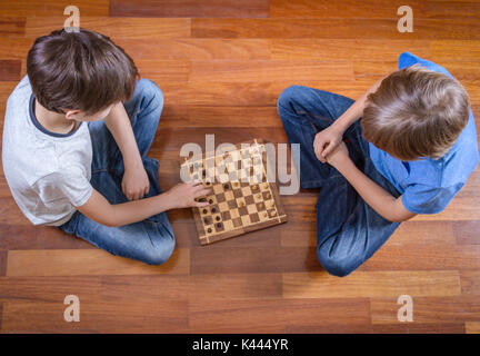 Enfants jouant aux échecs assis sur un plancher en bois. Vue d'en haut. Jeu, l'éducation, de vie, concept de loisirs Banque D'Images