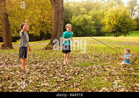 Deux jeunes garçons jouent au saut à la corde avec leur petit frère Banque D'Images