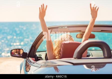 Heureux et insouciant femme dans la voiture sur la plage Banque D'Images