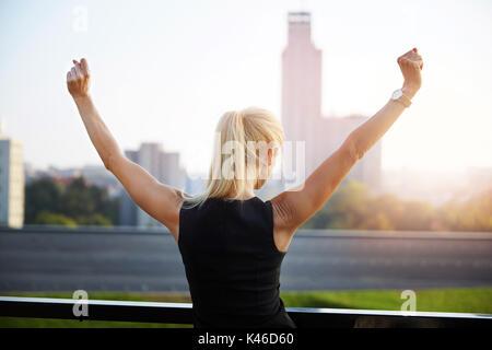 Retour portrait of businesswoman standing face à la vue sur la ville et d'élever les mains dans un geste de victoire. Banque D'Images