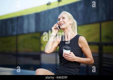 Portrait of businesswoman having pause avec café et talking on mobile. Banque D'Images