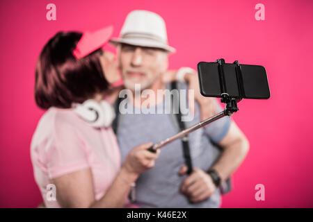 Selective focus of senior woman kissing mari tout en tenant isolé selfies sur Rose Banque D'Images