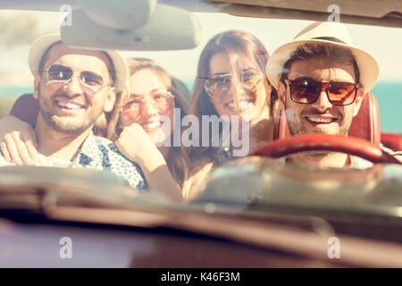 Belle fête ami filles dansant dans une voiture sur la plage heureux Banque D'Images