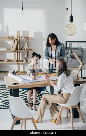 Groupe multiethnique de jeunes architectes professionnels travaillant avec blueprints in modern office