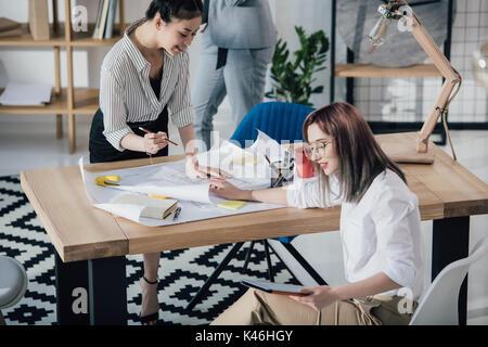 Jeunes architectes professionnels travaillant avec les bleus et digital tablet in modern office