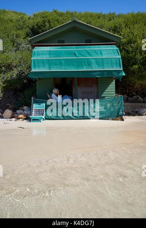 Vieille Femme est assise sur sa terrasse en face de sa baraque sur la plage Banque D'Images
