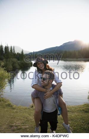 Jeune couple ludique usurpation de l'été ensoleillé à Lake Banque D'Images