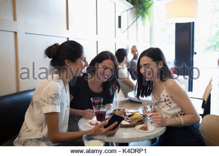 Smiling women friends drinking wine and using cell phone at cafe table Banque D'Images