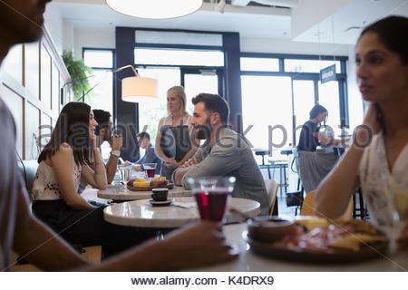 Les clients de manger et de boire du vin à table de café Banque D'Images