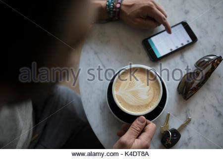 Vue de dessus l'homme de boire un cappuccino avec du lait et de feuille de mousse à l'aide de smart phone in cafe Banque D'Images