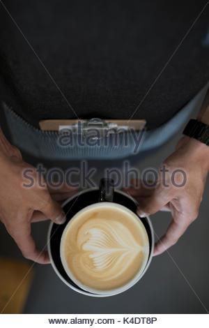 Vue aérienne de barista mâle holding cappuccino avec motif de feuilles de mousse de lait créative dans Coffee cup Banque D'Images