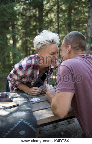 Affectionate couple kissing, des cartes à jouer à une table de pique-nique Camping Banque D'Images