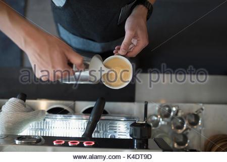 Vue aérienne de barista pouring mâle en mousse de lait cappuccino au café Banque D'Images