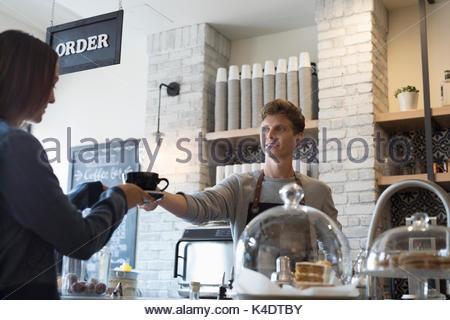 Servir le café barista mâle à femelle customer in cafe Banque D'Images