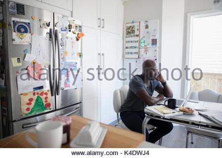 Mature african american man talking on cell phone et de travail à ordinateur portable à la table de cuisine Banque D'Images