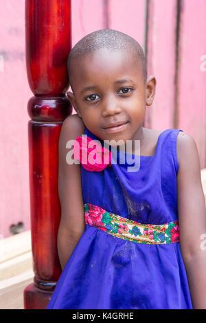 Une belle jeune fille en souriant. Elle est vêtue d'une robe bleue avec fleur rose sur l'épaule. Banque D'Images