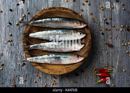 Tourné à angle élevé de certaines matières de sardines dans une plaque de bois, placé sur une table en bois rustique Banque D'Images
