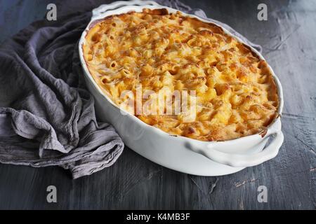 Angel haut Vue d'un plat de macaroni au fromage frais cuit avec tapis de table et de la vieille cuillère en bois rustique sur un fond sombre.