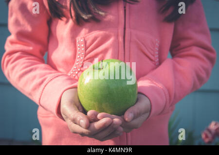 Jeune fille tenant une pomme verte dans ses mains à l'extérieur. Banque D'Images