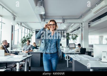 Portrait of smiling businesswoman standing in modern office. Belle jeune femme dans les verres au travail. Banque D'Images