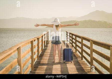Super vacances. jeune femme à bras ouverts et valise en attendant le bateau sur le quai Banque D'Images