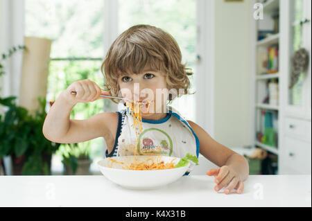 Portrait of a cute jeune garçon faire un gâchis tout en mangeant des pâtes pour le déjeuner Banque D'Images