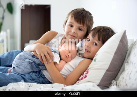 Deux enfants, tout-petit et son grand frère, étreignant et embrassant leurs nouveau-né frère à la maison, quelques Banque D'Images