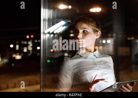 Businesswoman with tablet travailler tard dans la nuit. Banque D'Images
