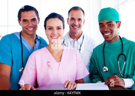 Portrait de réussite d'une équipe médicale au travail contre close-up de ruban de la sensibilisation au cancer de Banque D'Images