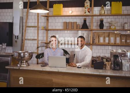 Portrait of smiling waitress et propriétaire de sexe masculin à l'aide d'ordinateur portable au comptoir dans un Banque D'Images