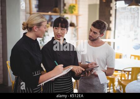 Le personnel d'attente les jeunes discuter sur tablet computer while standing at coffee shop