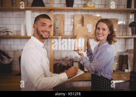 Portrait of smiling male propriétaire et serveuse l'organisation des paquets sur la durée du coffee shop Banque D'Images