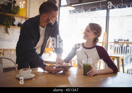 Young man holding tablet computer debout par woman sitting at table in coffee shop Banque D'Images
