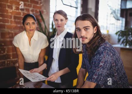 Portrait of young creative team standing avec les documents du coffee shop