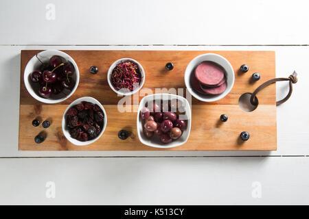 Portrait de betterave tranche avec divers fruits dans des bols sur une planche à découper Banque D'Images