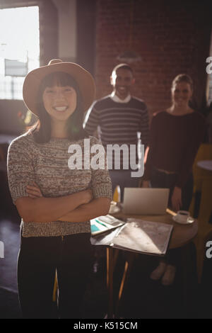 Portrait of smiling young woman wearing hat standing with arms crossed contre des collègues du coffee shop Banque D'Images