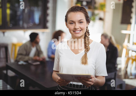 Portrait of smiling young waitress standing avec menu au café Banque D'Images