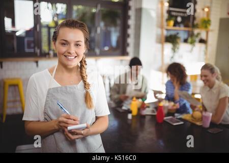 Portrait of smiling young waitress avec le bloc-notes au café permanent Banque D'Images
