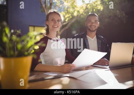 Portrait of smiling young professionnels créatifs de pointage à l'ordinateur à la table à café Banque D'Images