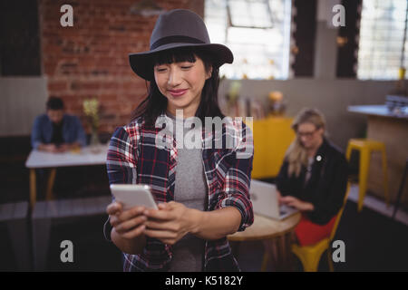 Smiling young attractive woman using mobile phone while standing at coffee shop Banque D'Images