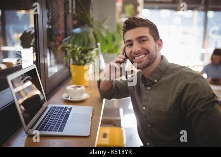 Portrait of smiling young man de tout smartphone at cafe Banque D'Images
