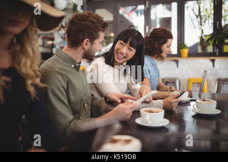 Smiling young friends talking while sitting at table in cafe Banque D'Images