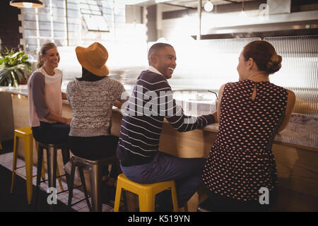 Cheerful young friends sitting compteur table in coffee shop Banque D'Images