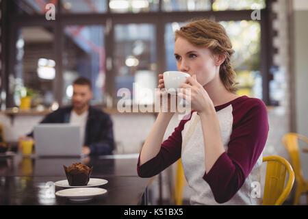 Belle jeune femme de boire du café à partir de la tasse alors que sitting at table in cafe Banque D'Images