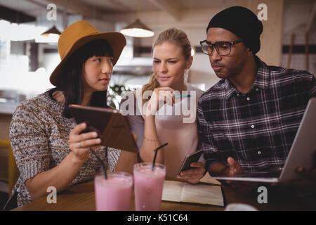 Young woman showing digital tablet à vos amis tout en étant assis à table dans un café