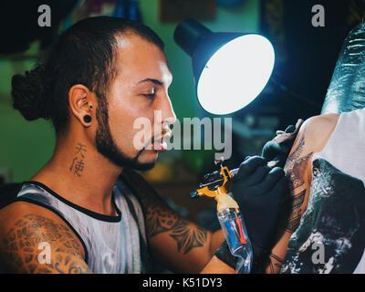 Portrait d'un homme maître de tatouage avec des dreadlocks montrant processus de création tatouage sur le corps Banque D'Images